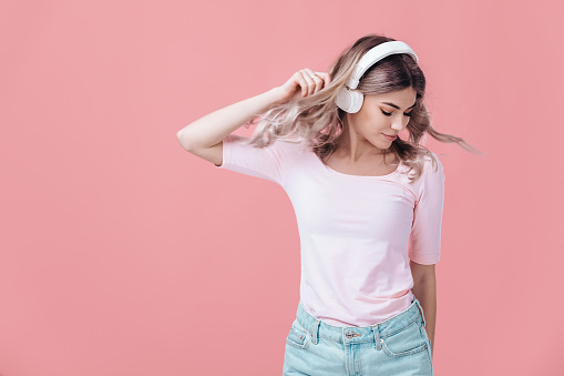 beautiful blonde woman in pink t-shirt and white headphones listens to music and smiling with closed eyes on pink background