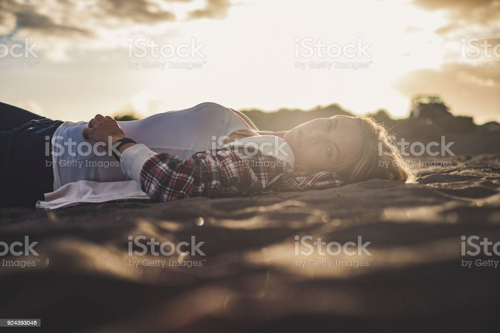 Beautiful sunset light for a cute blonde girl lay down rest on the...