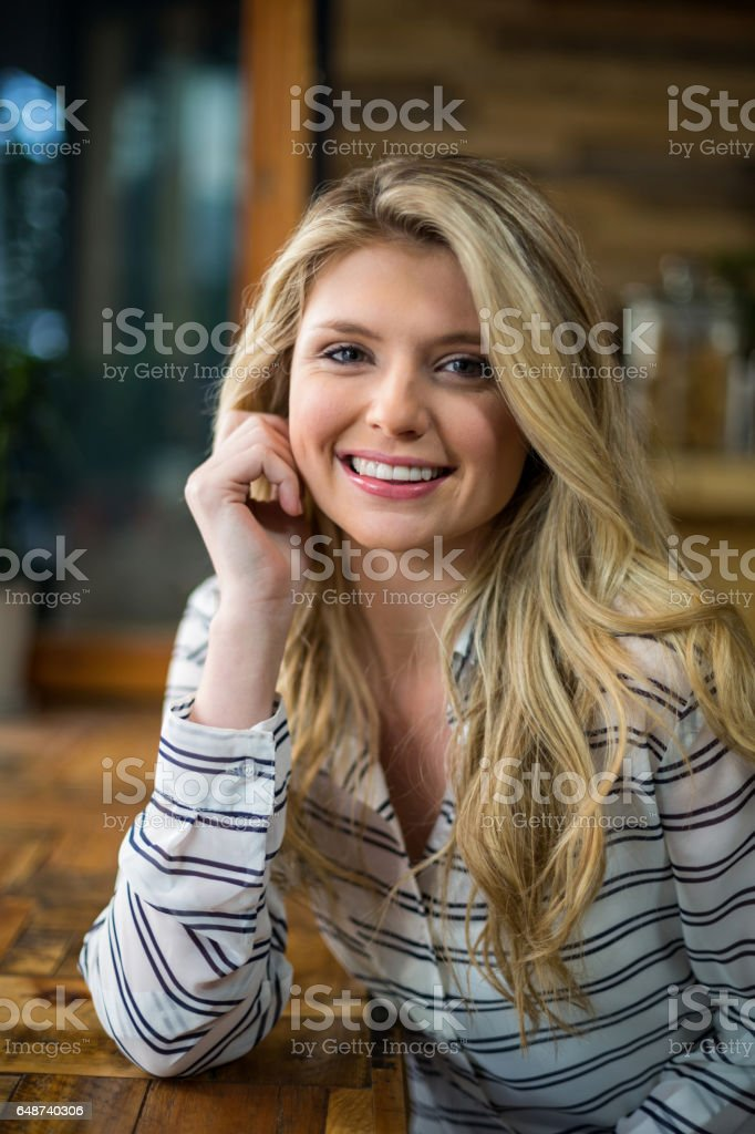 Beautiful blonde woman leaning on table in café stock photo