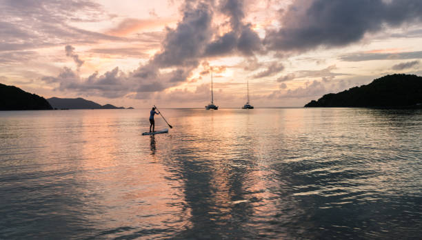 Beautiful blonde woman on stand up paddle board on holiday during sunset with yachts in the background in the British Virgin Islands, Caribbean. stock photo