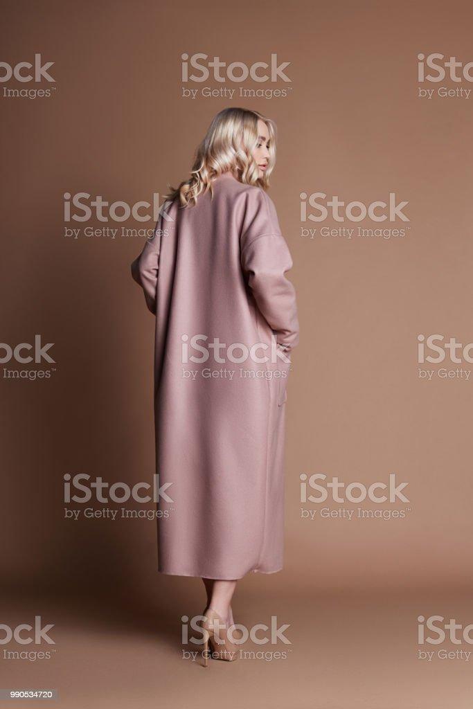 dff954281a14e Belle femme blonde posant dans un manteau rose sur fond beige. Défilé de  mode vêtements