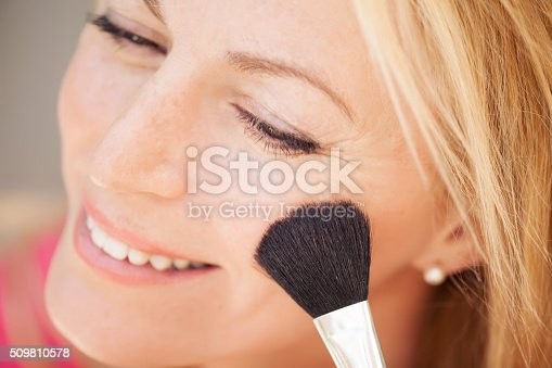 istock beautiful blonde woman putting on make up 509810578