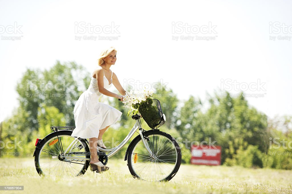 Beautiful blonde woman riding a bicycle. royalty-free stock photo