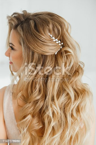 Beautiful blonde woman showing her perfect greek hairstyle and purple colored crystal earrings with beads. in beige posing in studio room.