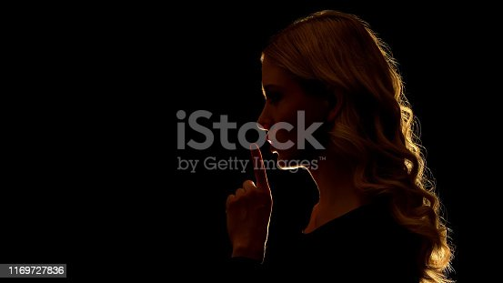 istock Beautiful blonde woman showing silence sign, mysterious secret, side view 1169727836