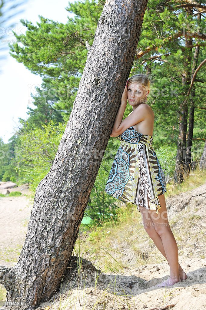 Beautiful blonde woman standing at the tree royalty-free stock photo