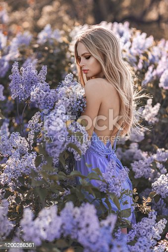 1054970060 istock photo Beautiful blonde woman surrounded by blue flowers 1200286361