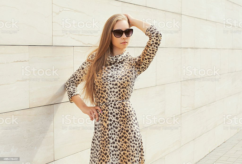 Beautiful blonde woman wearing a leopard dress and sunglasses po stock photo