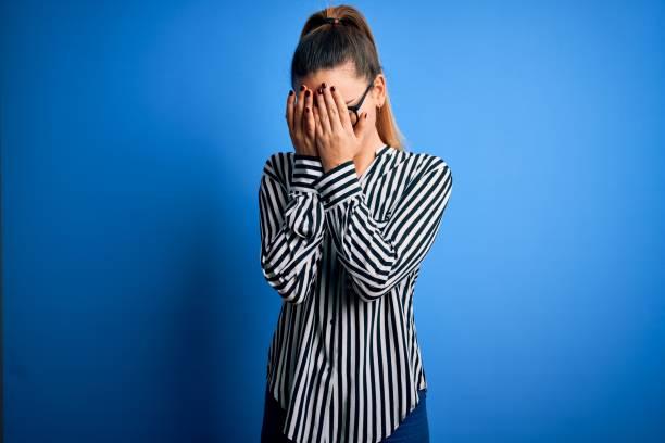 hermosa mujer rubia con ojos azules con camisa a rayas y gafas sobre fondo azul con expresión triste cubriendo la cara con las manos mientras llora. concepto de depresión. - vergüenza fotografías e imágenes de stock