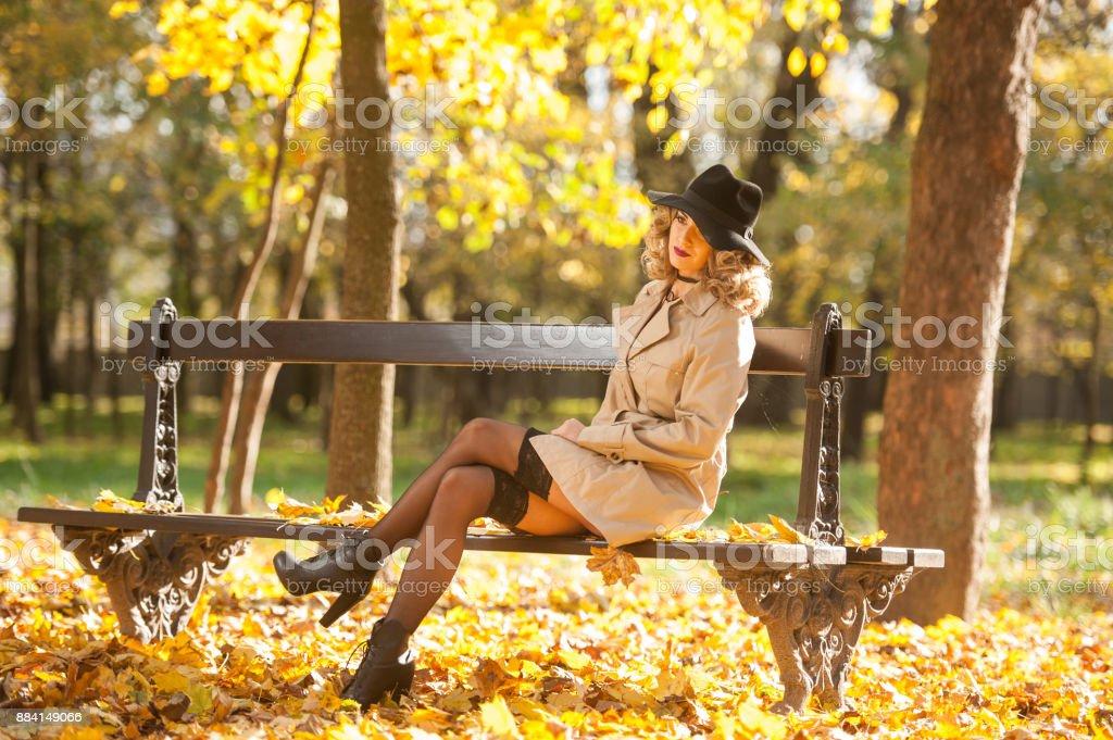 schöne blonde Frau mit Mantel, lange Beine in schwarzen Strumpf und schwarzen Hut in einem Herbst-Szene. Porträt eines sehr schöne elegante und sinnliche Frau mit lockigem Haar und Strumpf posiert im Park. – Foto