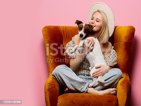 Beautiful blonde womanwith a dog in an armchair on pink background