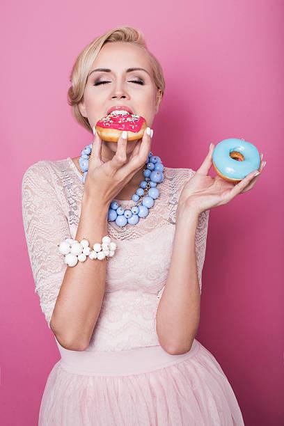 schöne blonde frau isst bunte dessert. mode schuss. weiche farben - modetorten stock-fotos und bilder
