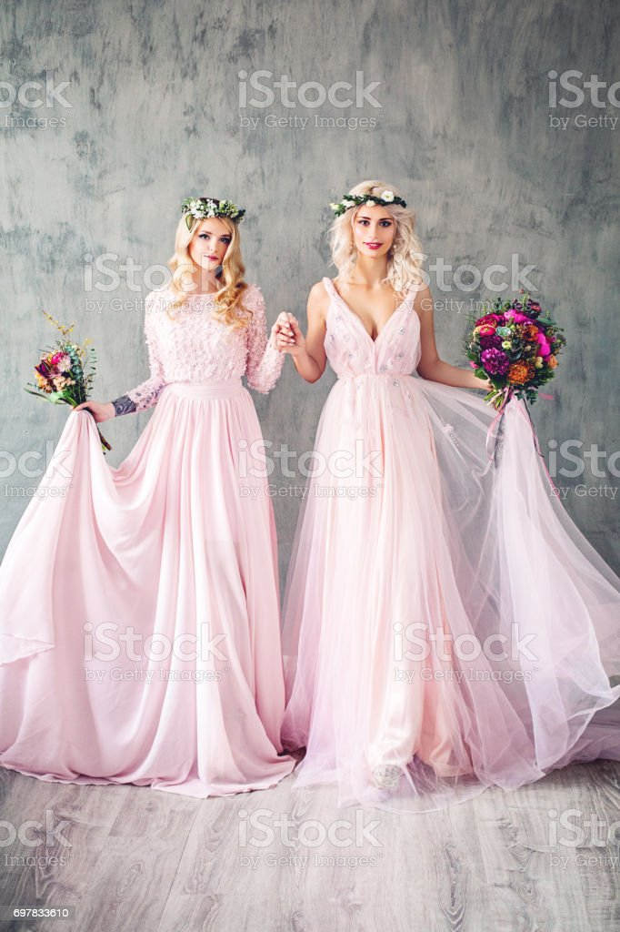Beautiful Blonde Women in Pink Evening Gown Smiling. Perfect Hairstyle, Makeup and Summer Flowers stock photo