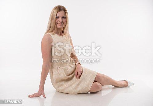 673361134 istock photo Beautiful blonde women sittin on white background 1187625769