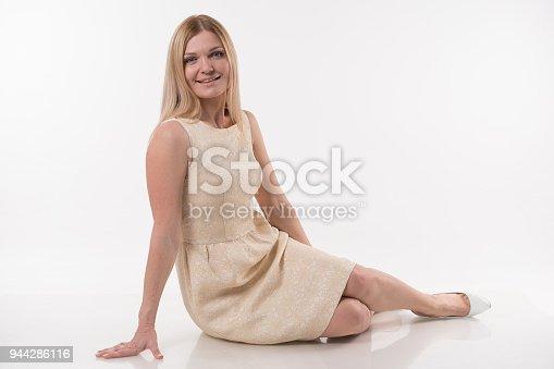 673361134 istock photo Beautiful blonde women sittin on white background 944286116
