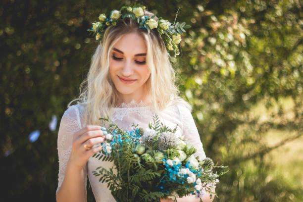 yaz aylarında açık havada beyaz gelinlik kafasına çiçek buketi ve çelenk ile güzel sarışın genç gelin portresi - beyaz elbise stok fotoğraflar ve resimler
