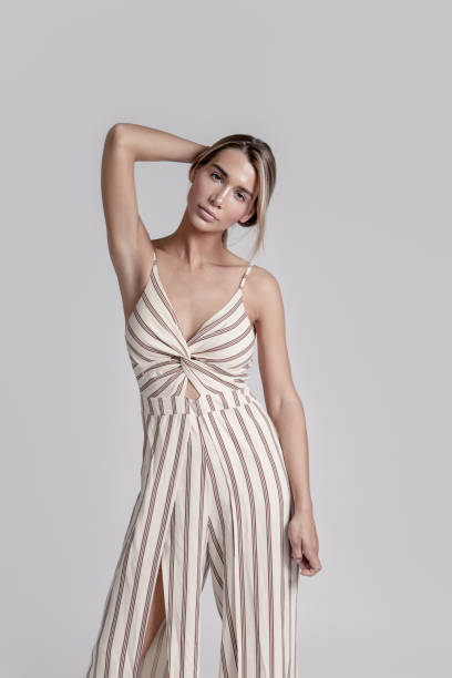 Beautiful blonde young woman in luxury striped sleeveless jumpsuit Portrait of young beautiful brunette woman with professional make-up looking fresh and lovely luxury striped sleeveless jumpsuit on gray background nude women pics stock pictures, royalty-free photos & images