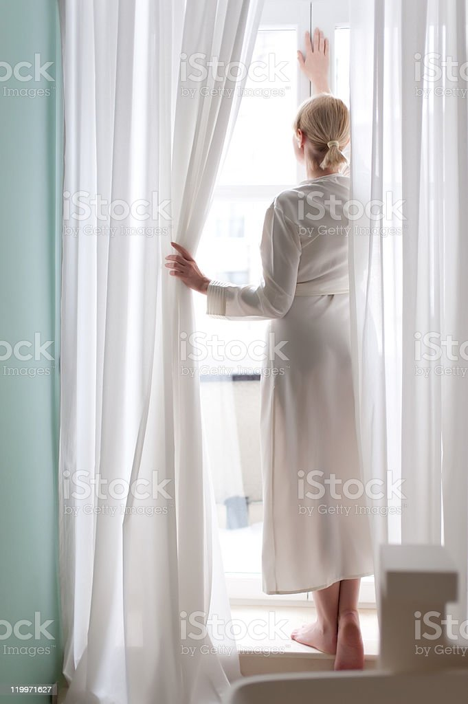 Beautiful blonde young woman, silk bathrobe, standing by the window royalty-free stock photo