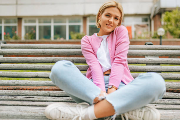 Beautiful blonde young woman smiling broadly, wearing blue jeans, white t-shirt and pink jacket, smiling and sitting on the bench in the city street. Happy female resting outside in spring time. stock photo