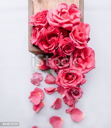 istock Beautiful blossoming pink roses look like growing out of small rustic the wooden box, top view 944615232