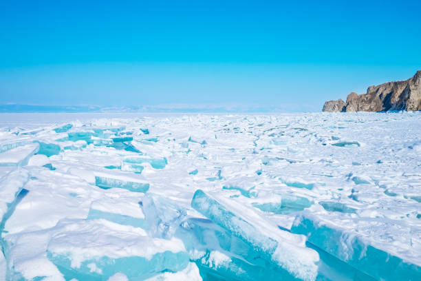 Beautiful blue ice on the Frozen Lake Baikal with mountains on the background. stock photo