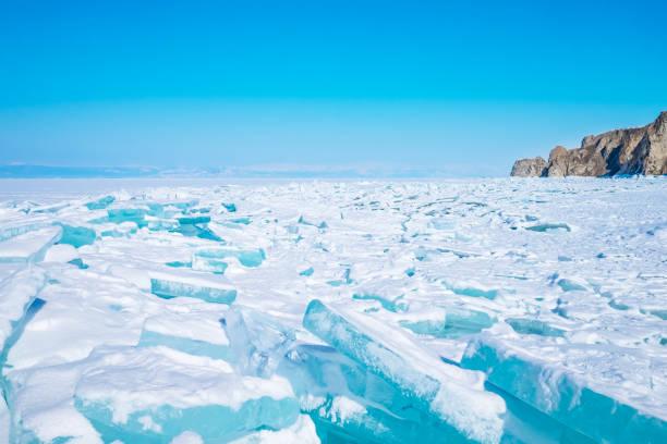 Schöne blaue Eis auf dem gefrorenen See Baikal mit Bergen im Hintergrund. – Foto