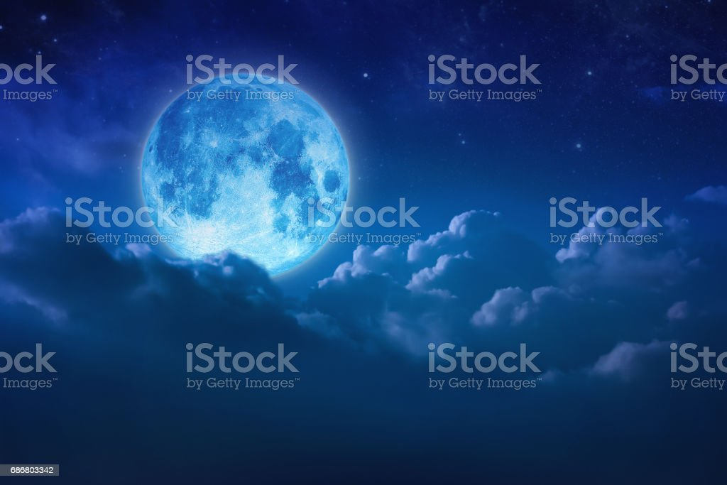 Beautiful blue moon behind cloudy on sky and star at night. Outdoors at night. Full lunar shine moonlight over cloud at nighttime with copy space background for headline text and graphic design. stock photo