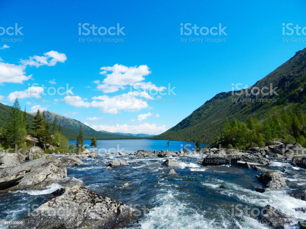 Beautiful blue mountain lake with a river flowing inti it 免版稅 stock photo