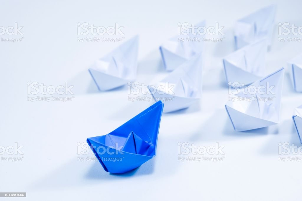 Beautiful blue paper ship move forward among white ships on white...