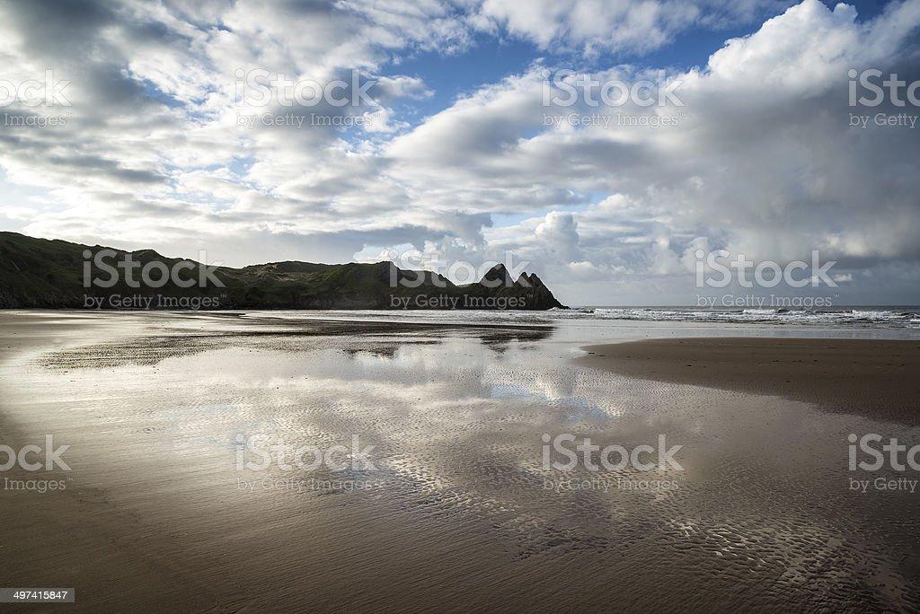 Beautiful blue sky morning landscape over sandy Three Cliffs Bay royalty-free stock photo