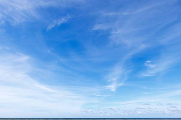 Beautiful blue sky over the sea with translucent, white, Cirrus clouds stock photo