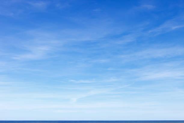 beau ciel bleu avec des nuages de cirrus au-dessus de la mer. horizon. - bleu photos et images de collection
