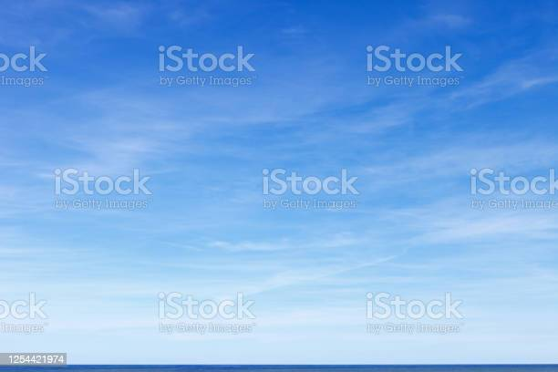 Photo of Beautiful blue sky with cirrus clouds over the sea. Skyline.
