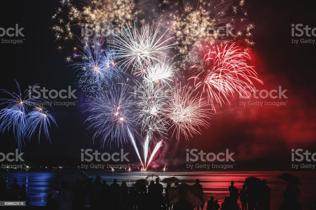 Beautiful blue white and red firework pyrotechnics show like french flag colors with unrecognizable crowd silhouettes watching stock photo