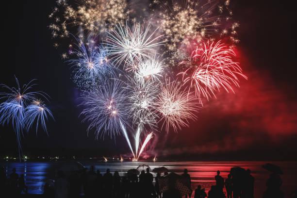 Beau bleu blanc et rouge pyrotechnie feu d'artifice comme français des couleurs du drapeau avec des silhouettes de foule méconnaissable regarder - Photo