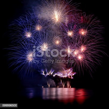 istock Beautiful blue white and red large fireworks with water reflections 599996500