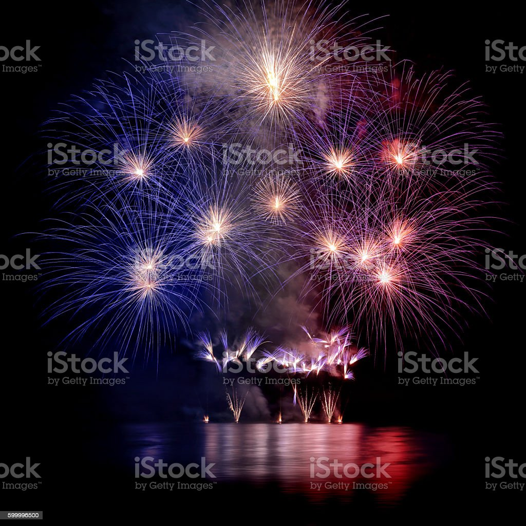 Beautiful blue white and red large fireworks with water reflections stock photo