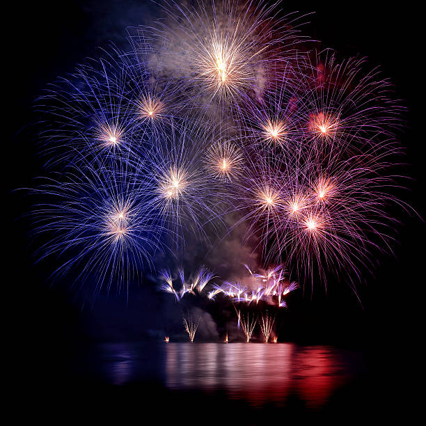 Beautiful blue white and red large fireworks with water reflections - Photo