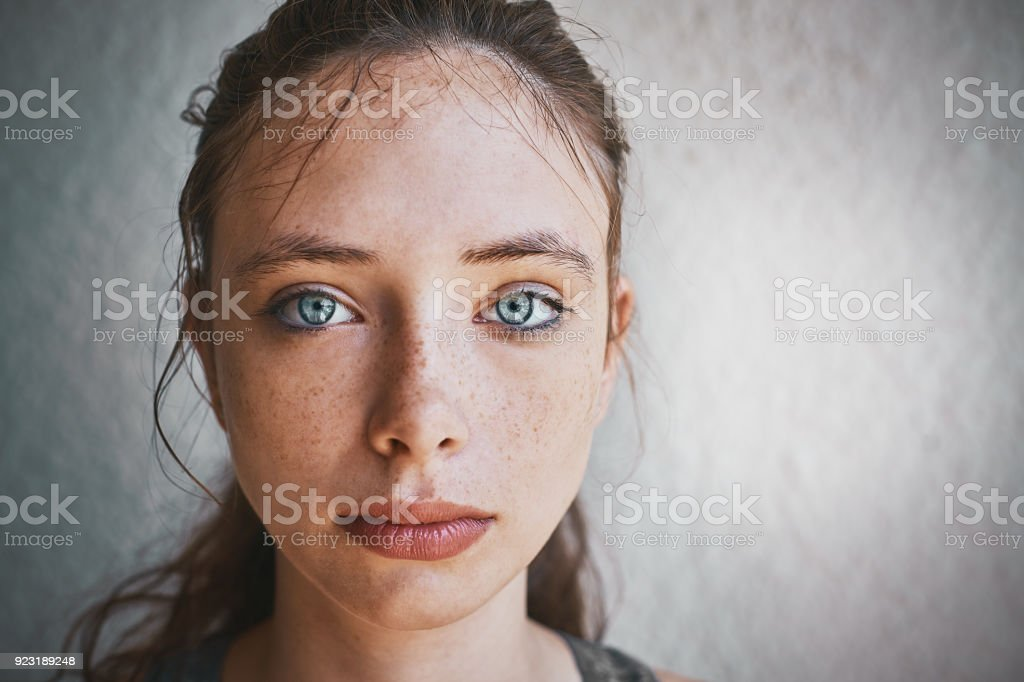 Beautiful blue-eyed brunette standing by textured wall looks sad stock photo