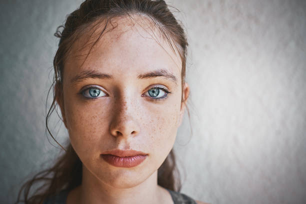 mooie brunette staande blauwogige door getextureerde muur ziet er triest - vrouw verdrietig stockfoto's en -beelden