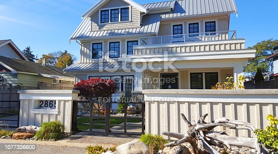 Crescent Beach,Surrey,British Columbia,Canada- October 6,2018: Exterior front view of large 3 story board and batten home. Also shingles and metal roof.
