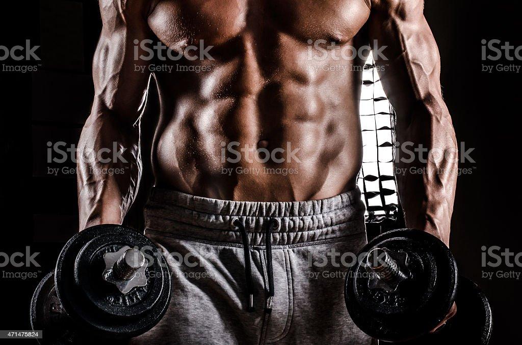 Magnifique mâle avec des poids et haltères en action - Photo