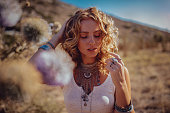 Young woman in boho style with freckles, silver jewelry and wavy hairstyle daydreaming in field