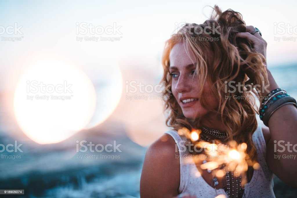 Beautiful boho girl celebrating with sparklers at beach at sunset stock photo