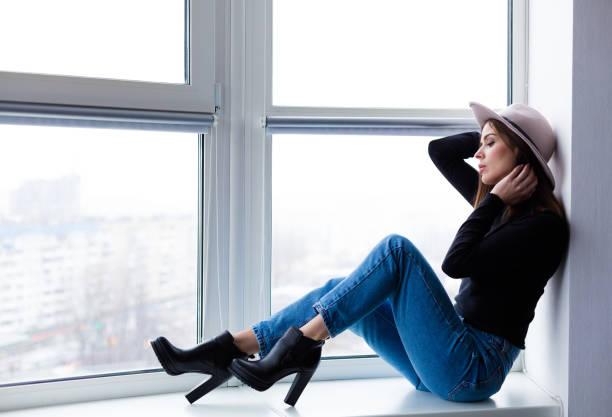 schöne boho frau in wollmütze am fenster sitzen - wintermantel damen wolle stock-fotos und bilder