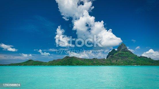 Beautiful Panorama of the turqoise lagoon of Bora Bora Island under blue summer sky. Mount Otemanu Volcanic Mountain Peak in the Background. Bora Bora Island, Society Islands, French Polynesia.