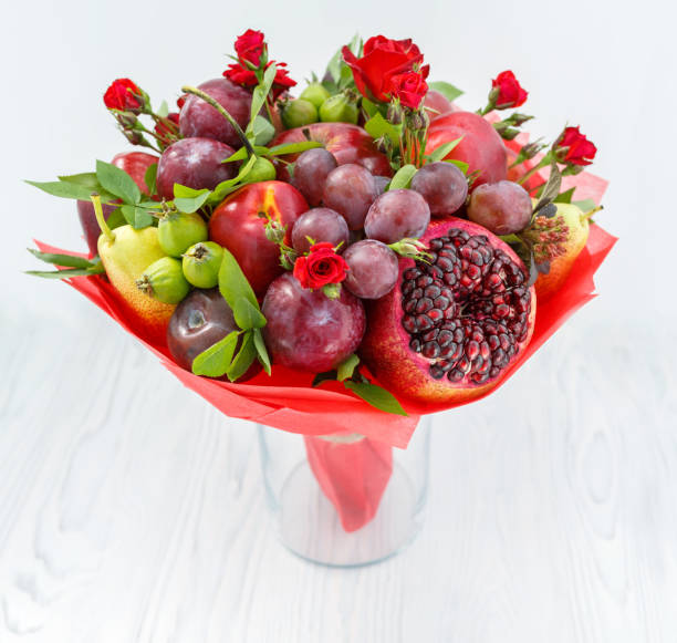 Beautiful bouquet consisting of pomegranate, apples, plums and scarlet roses standing in a vase on a wooden table stock photo