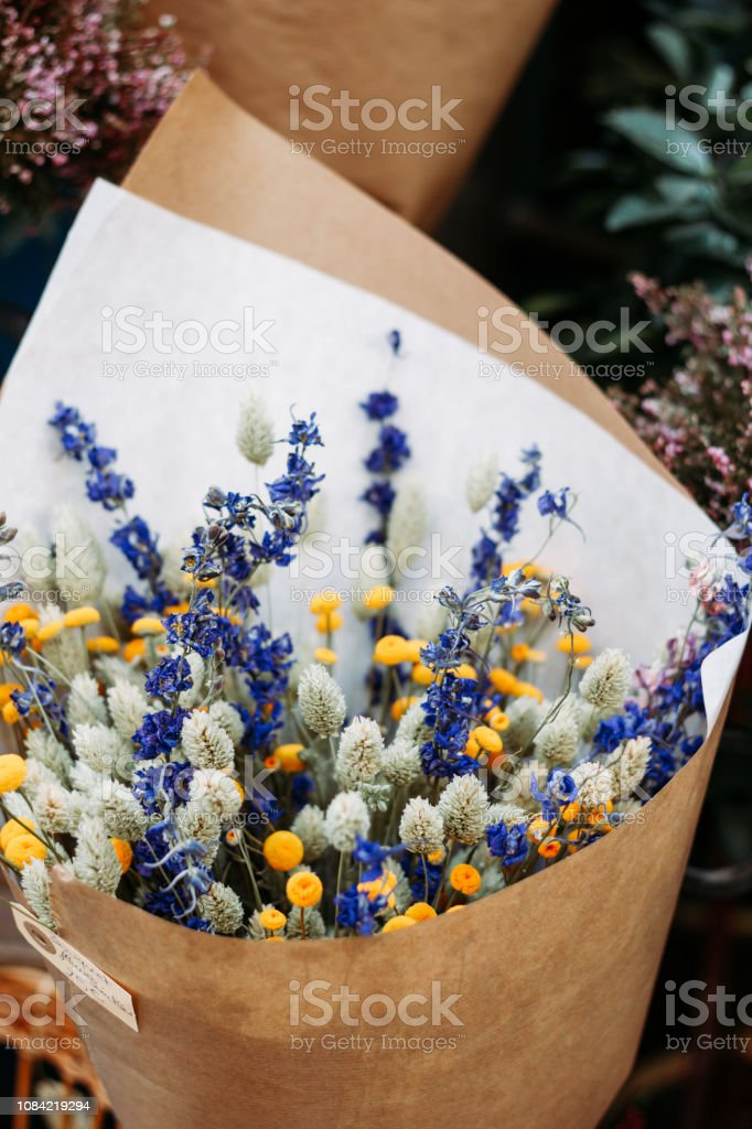Beautiful bouquet in a craft paper on a showcase in a French shop. The concept of Valentine's Day and greetings. stock photo