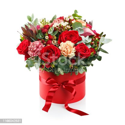 Beautiful bouquet in a red luxury present box with a red bow, isolated on white background