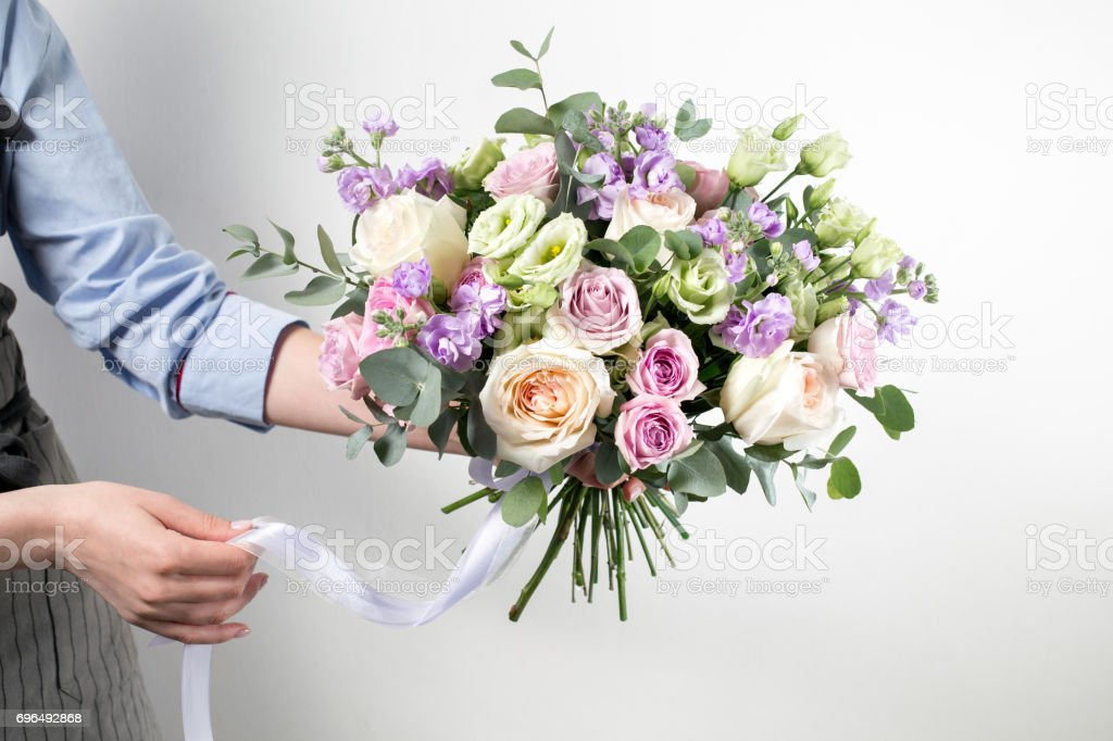 beautiful bouquet made of different flowers in young girl hand . colorful color mix flower. Work clothing in a blue shirt and gray apron